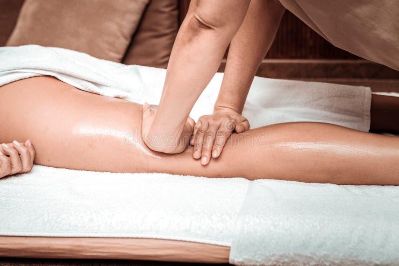 Koppla av benmassage med olja för massagesalongklient royaltyfri foto