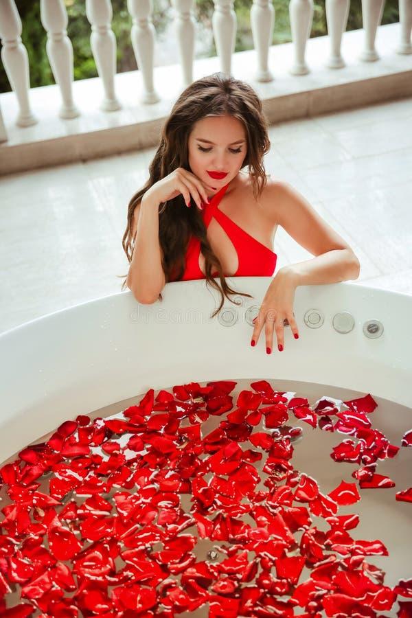 koppla av brunnsorten Härlig bikinikvinna som tycker om badet med röda rosa kronblad V?rd- och sk?nhet Sexig flicka i röd swimwea arkivfoton
