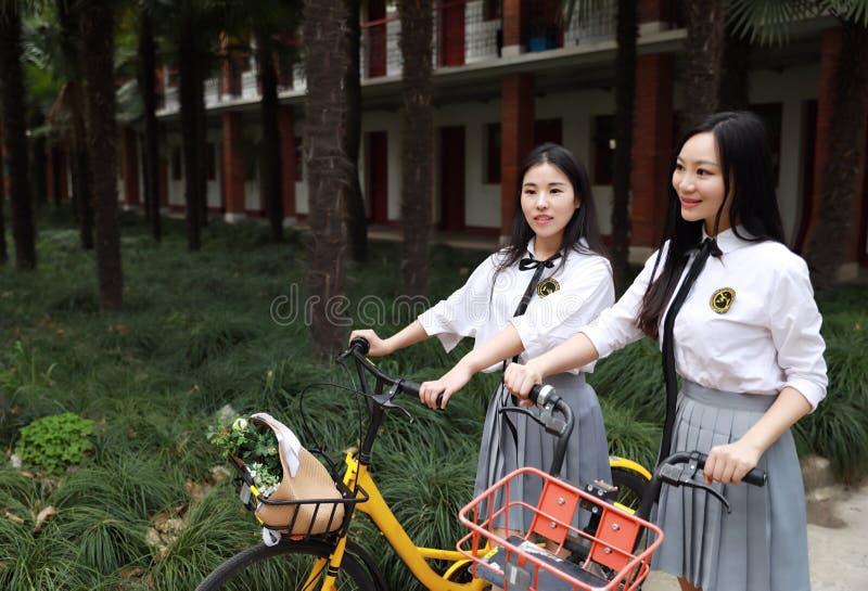Koppla av den asiatiska kinesiska nätta flickakläderstudenten som dräkten i skola tycker om rittcykeln för fri tid i naturvårträd royaltyfri fotografi
