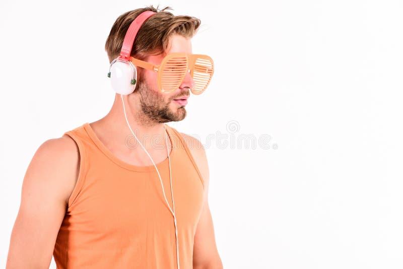 Koppla av den sexiga muskulösa mannen för playlisten för att lyssna musik från playlistman kopplar av i hörlurar som isoleras på  arkivfoton