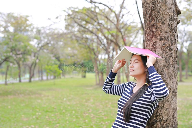 Koppla av den unga asiatiska kvinnan med ställeboken på hennes huvud parkera in det utomhus- anseendet lutar mot stamträd med stä arkivbild