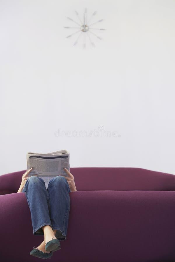 Koppla av för kvinna som är uppochnervänt på Sofa Reading Newspaper royaltyfri foto