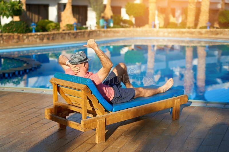 Koppla av i pölsommaren Ung och lyckad man i hatten som ligger på en soldagdrivare på hotellet på bakgrunden av solnedgången, beg royaltyfria foton