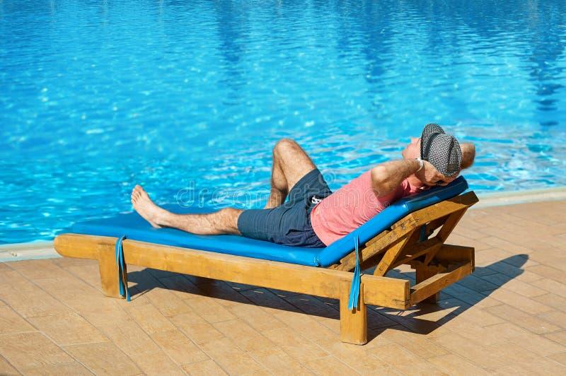 Koppla av i pölsommaren Ung och lyckad man i hatten som ligger på en soldagdrivare på hotellet på bakgrunden av solnedgången, beg arkivbild