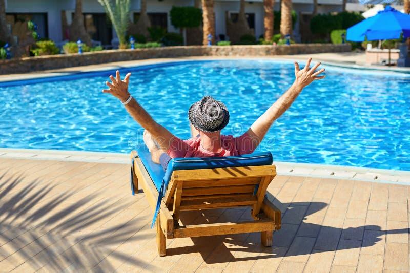 Koppla av i pölsommaren Ung och lyckad man i hatten som ligger på en soldagdrivare på hotellet på bakgrunden av solnedgången, beg arkivfoton