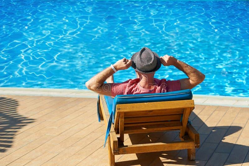 Koppla av i pölsommaren Ung och lyckad man i hatten som ligger på en soldagdrivare på hotellet på bakgrunden av solnedgången, beg arkivbilder