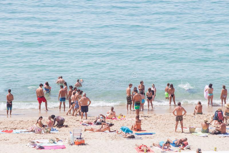 Koppla av med den perfekta sikten Folk på stranden och folk som simmar i Portugal royaltyfri fotografi