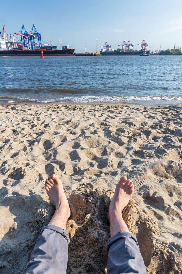 Koppla av med fot i sanden p? den Elbe stranden i Hamburg med beh?llarehamnen i bakgrunden arkivfoton