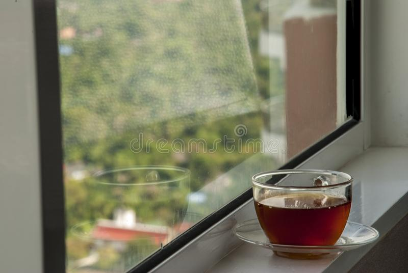 Koppla av med kaffe vid fönstret arkivbilder