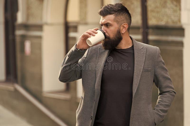 Koppla av och ladda upp Sk?ggig hipster f?r man som dricker kaffepapperskoppen En mer smutt av kaffe Dricka kaffe p? g? fotografering för bildbyråer