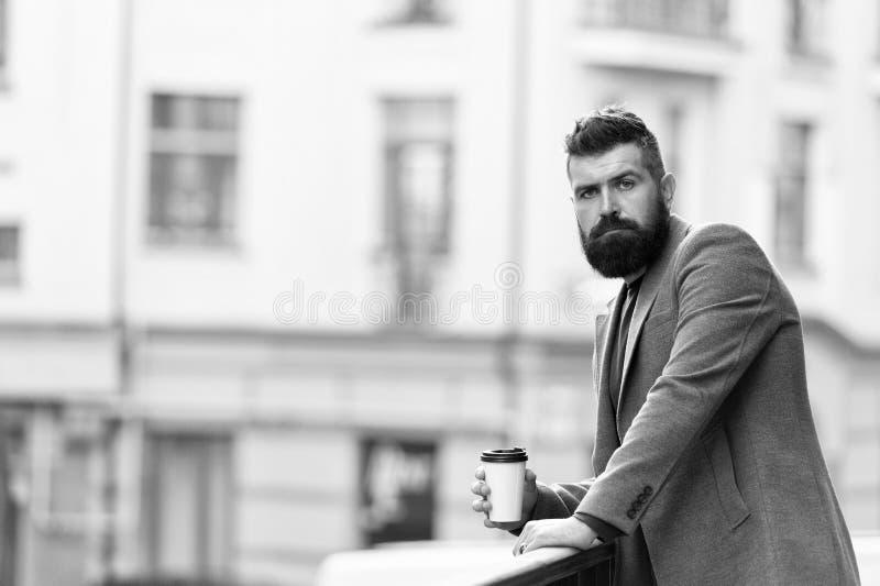 Koppla av och ladda upp Sk?ggig hipster f?r man som dricker kaffepapperskoppen En mer smutt av kaffe Tycka om kaffe p? g? arkivbild