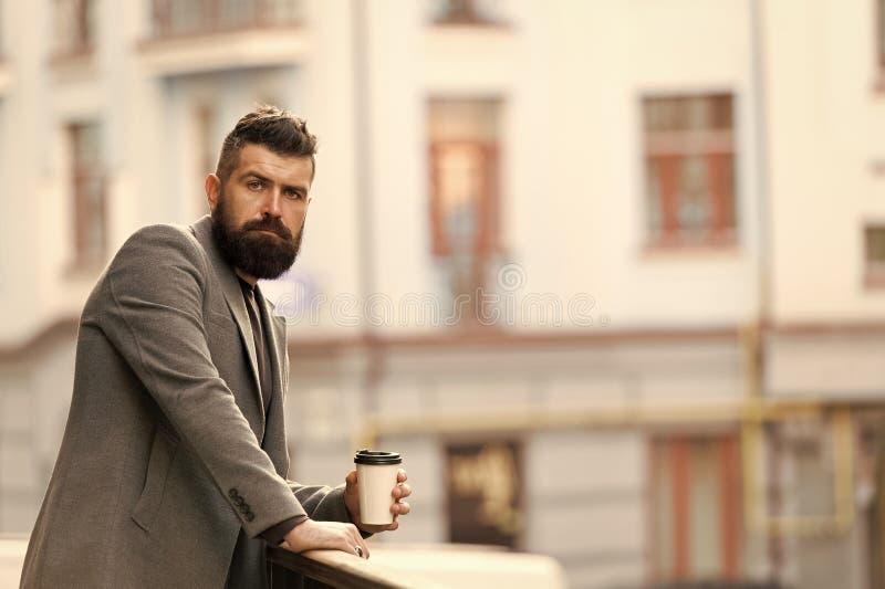 Koppla av och ladda upp Sk?ggig hipster f?r man som dricker kaffepapperskoppen En mer smutt av kaffe Tycka om kaffe p? g? royaltyfri fotografi