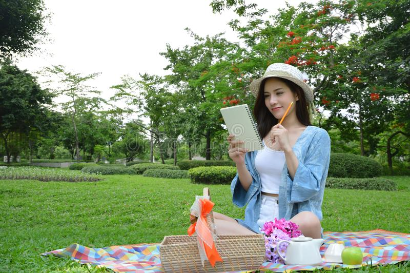 Koppla av och tänkande framtida plan för härlig nätt asiatisk kvinna för att skriva något på dagbokboken med leendeframsidan i tr royaltyfri foto