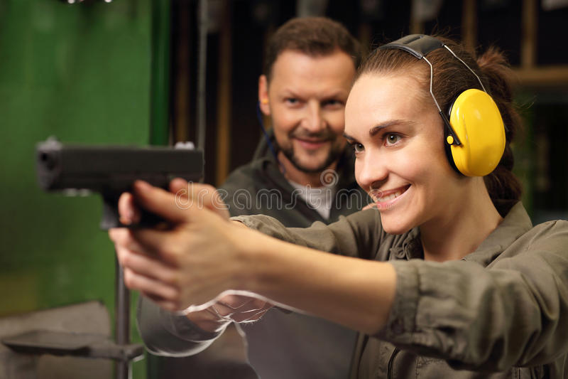 Koppla av på skyttet, en kvinna som skjutas med en Glock royaltyfria bilder