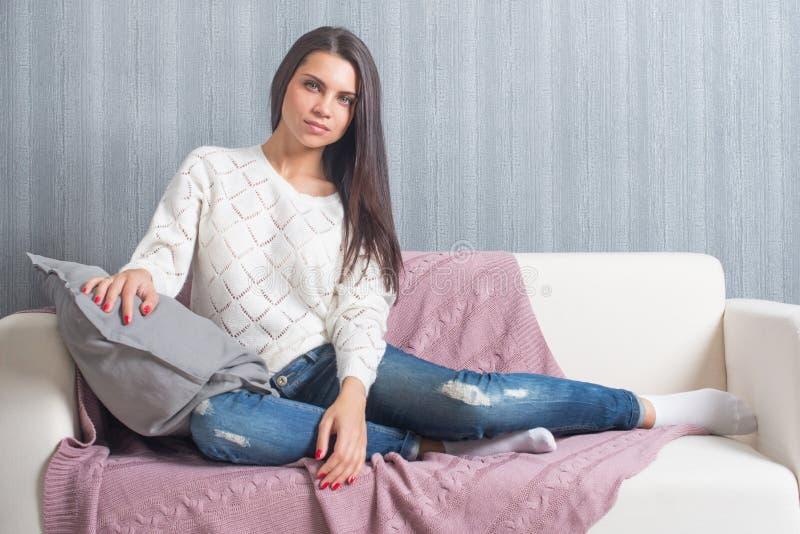 Koppla av på soffan, soffa hemma, komfort gulligt le för ung kvinna, royaltyfri fotografi