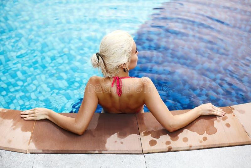 Koppla av på strandsemesterort Härlig blond kvinna som tycker om sommar i simbassäng Lyxigt lopp- och turismbegrepp royaltyfri fotografi