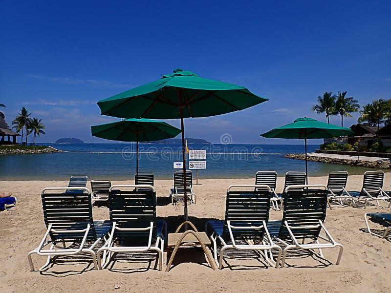 Koppla av p? den vita sandiga stranden p? bekv?m lat stol under den soliga dagen royaltyfri bild