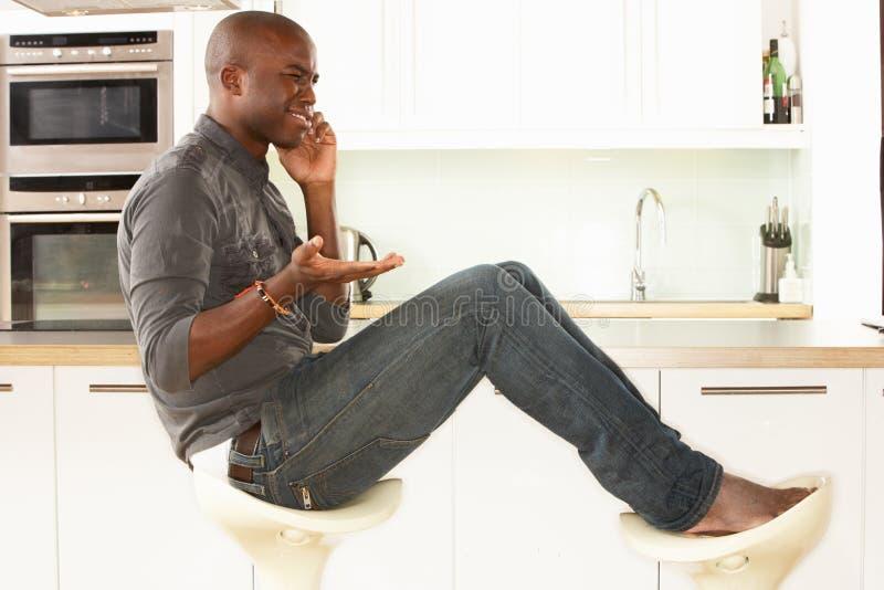 koppla av sittande samtal för kökmantelefon royaltyfria foton