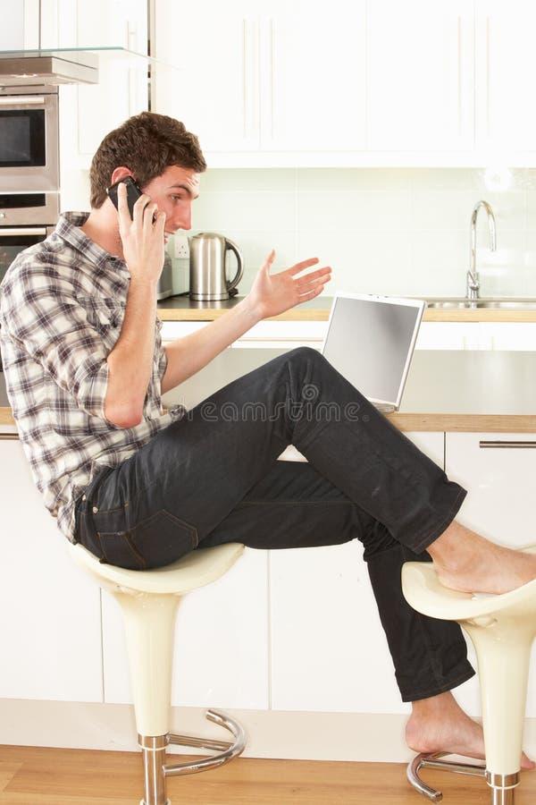 koppla av sittande samtal för kökmantelefon royaltyfria bilder