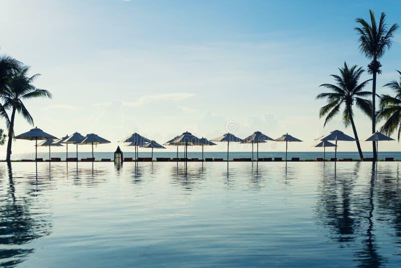 Koppla av stolar bredvid av simbassäng nära havet i lyxig semesterort eller hotell Sommar-, lopp-, semester- och feriebegrepp royaltyfri fotografi