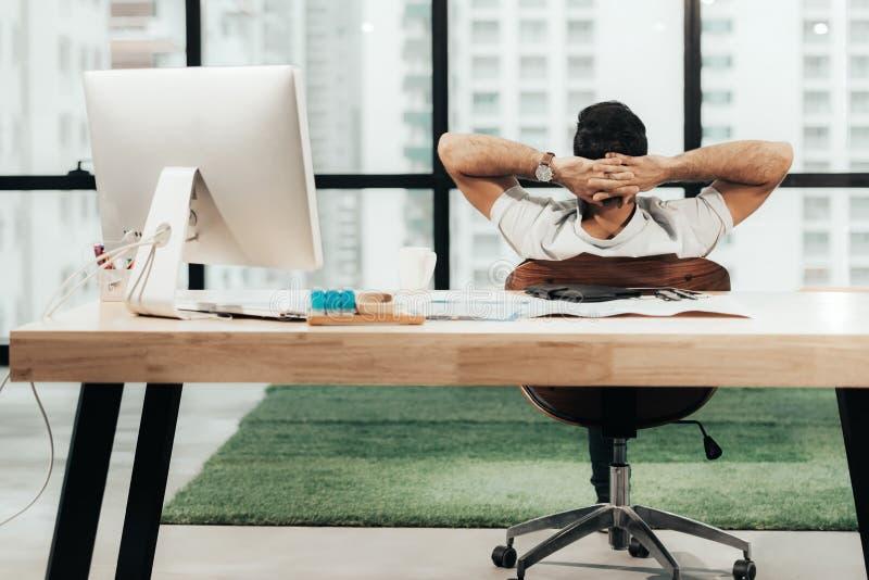 koppla av tid Lyckad affärsman som kopplar av och vilar, når att ha suttit och hårt att ha arbetat i modernt kontor Sund omsorg f royaltyfria foton