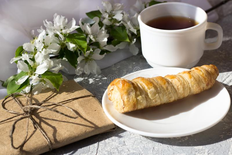 Koppla av tid och lycka med kopp te med bland den nya vårblomman arkivbild