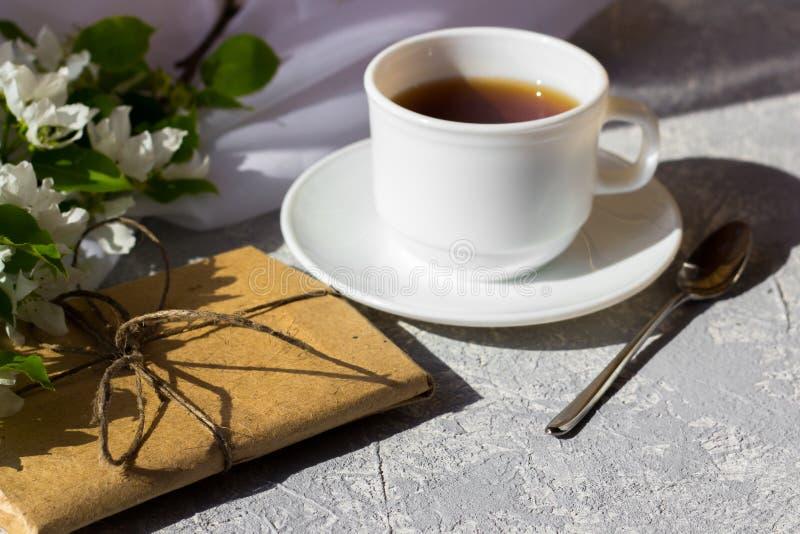 Koppla av tid och lycka med kopp te med bland den nya vårblomman royaltyfria bilder