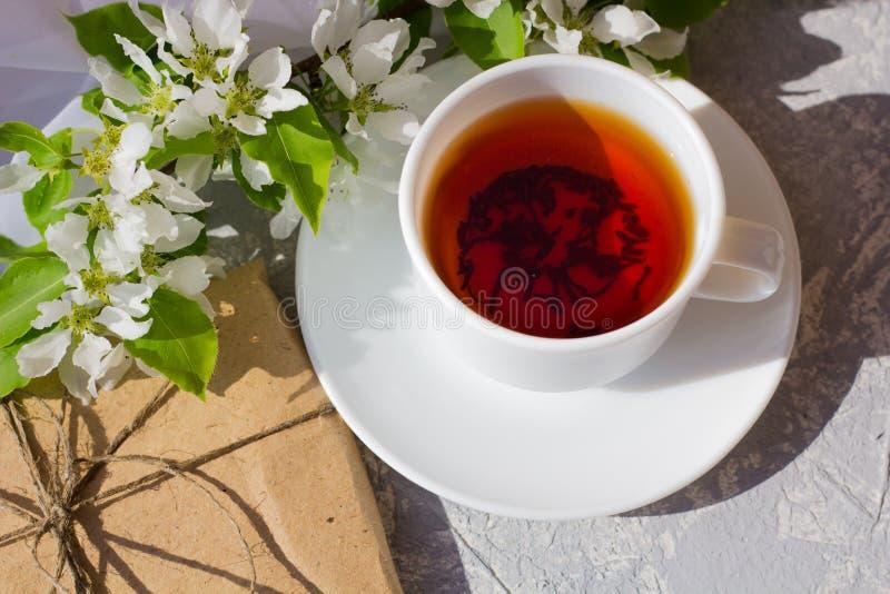Koppla av tid och lycka med kopp te med bland den nya vårblomman arkivfoton