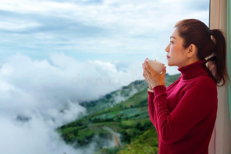 Koppla av vinterstil Den asiatiska kvinnan med ny morgon för röd tröja som dricker varmt kaffe och ut ser fönstret för, ser berge royaltyfri foto