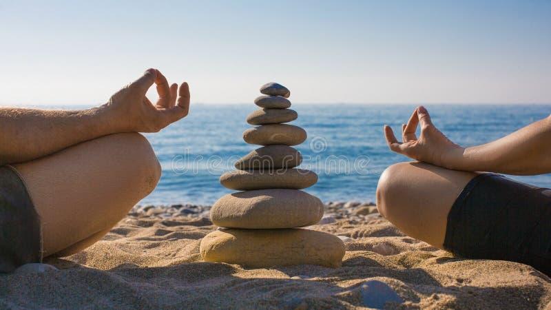 Koppla ihop ?vande yoga p? stranden stillhet kopplar av zen royaltyfria foton