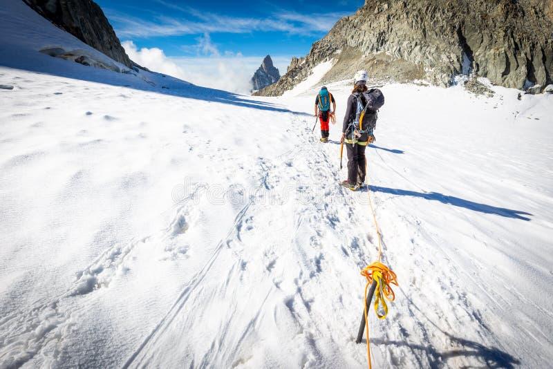 Koppla ihop alpinistbergsbestigare som g?r glaci?rlutningar MONT BLANC arkivbild