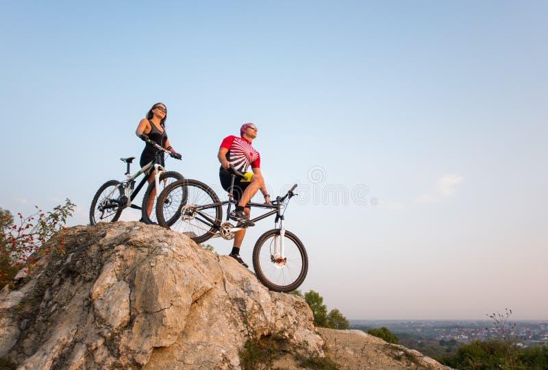 Koppla ihop anseendet med cyklar på vagga under aftonhimmel arkivfoton