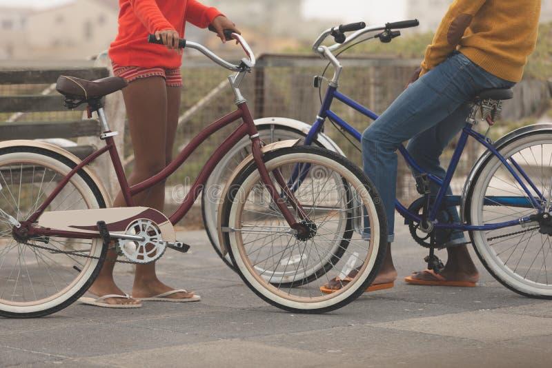Koppla ihop anseendet, medan rymma cykeln på promenad royaltyfri foto