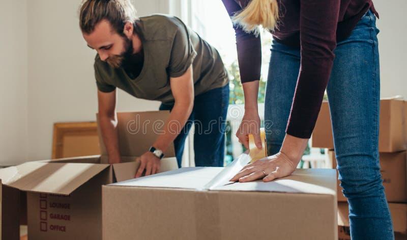Koppla ihop arbete tillsammans, i inpackning av deras hushållobjekt i boxe arkivbilder