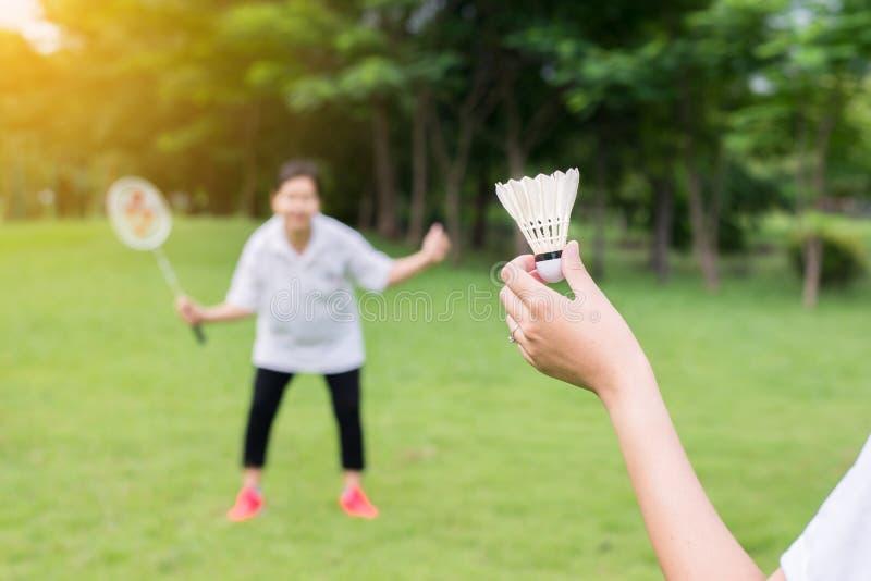 Koppla ihop asiatiska kvinnahänder som rymmer badmintonracket, och fjäderbollen parkerar, stänger sig offentligt upp arkivfoton