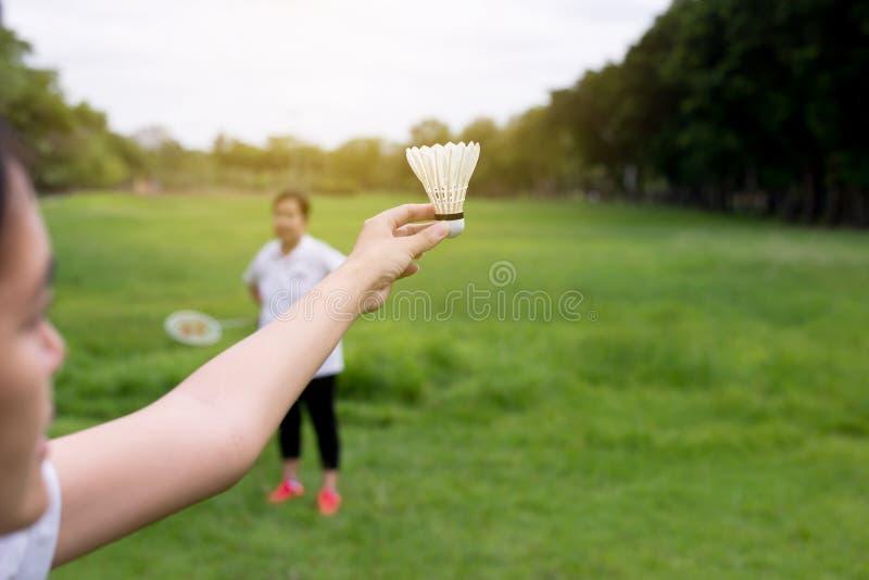 Koppla ihop asiatiska kvinnahänder som rymmer badmintonracket, och fjäderbollen parkerar, stänger sig offentligt upp arkivbilder