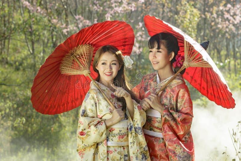 Koppla ihop asiatiska kvinnor som bär den traditionella japanska kimonot och röd u royaltyfri foto