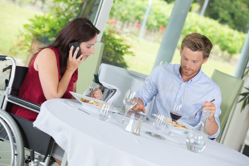Koppla ihop att äta middag i destinerad dam för restaurangrullstol på telefonen arkivfoto