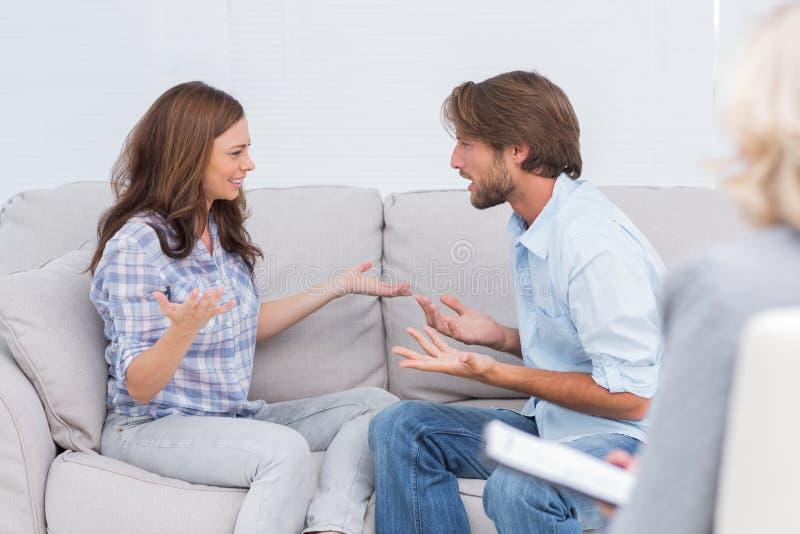 Koppla ihop att argumentera, medan terapeuten lyssnar till dem royaltyfria bilder