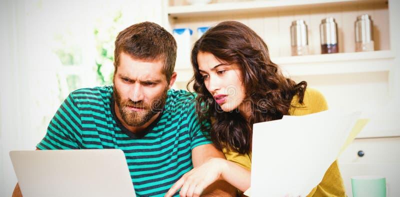 Koppla ihop att betala deras räkningar med bärbara datorn i kök arkivfoto