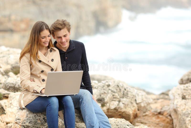 Koppla ihop att dela en bärbar dator på stranden på ferier royaltyfri fotografi