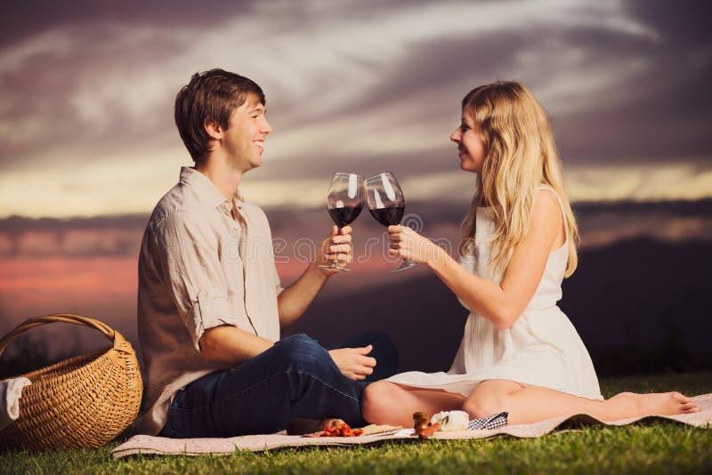 Koppla ihop att dricka exponeringsglas av vin på romantisk solnedgångpicknick royaltyfria foton
