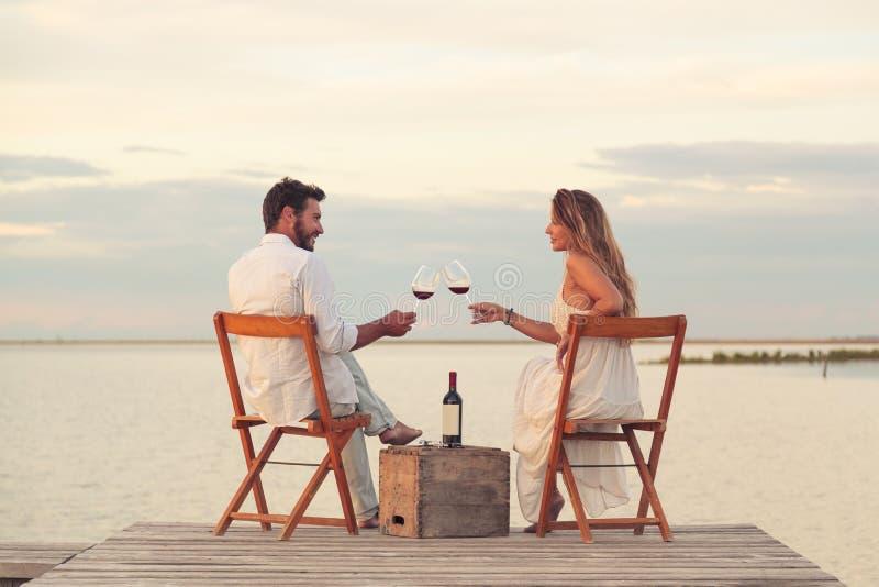 Koppla ihop att dricka rött vin på sjösidan på en brygga royaltyfria bilder
