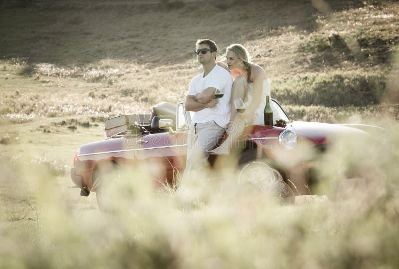 Koppla ihop att dricka vin i ett gräsfält på en tappningsportbil royaltyfri bild