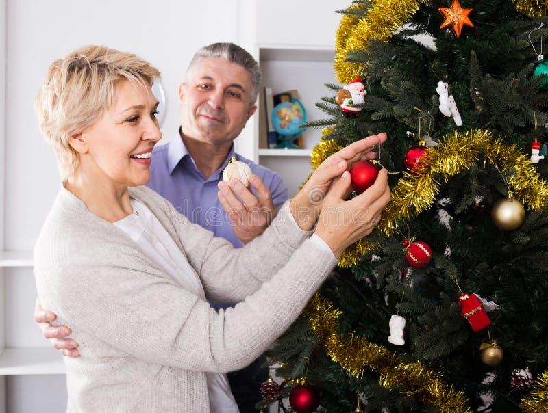 Koppla ihop att förbereda sig att fira i hans hem- jul och nya år arkivfoto