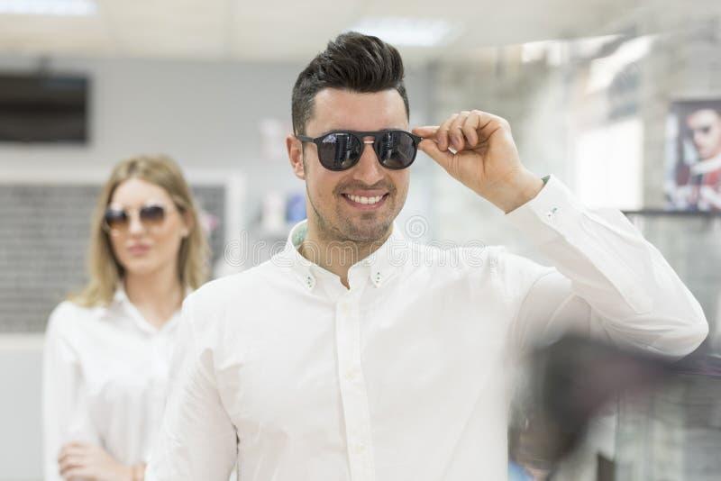 Koppla ihop att försöka på solglasögon i optiskt glasögonlager arkivfoto