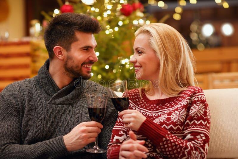Koppla ihop att fira jul som rostar med exponeringsglas av rött vin royaltyfria bilder