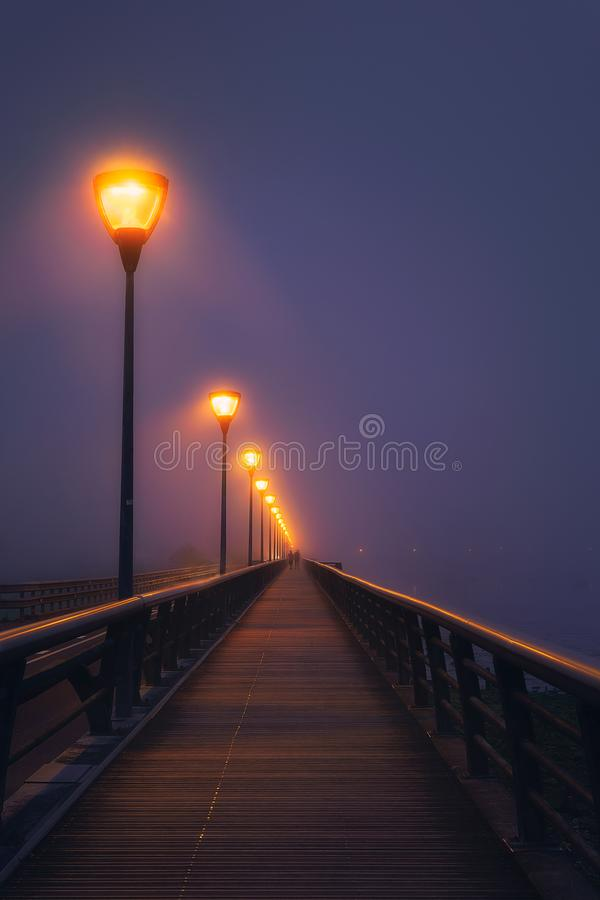 Koppla ihop att gå på den mörka gatan som är upplyst med streetlamps arkivfoto