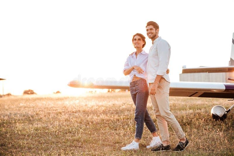 Koppla ihop att gå tillsammans över fältet med flygplanet på bakgrund arkivbild
