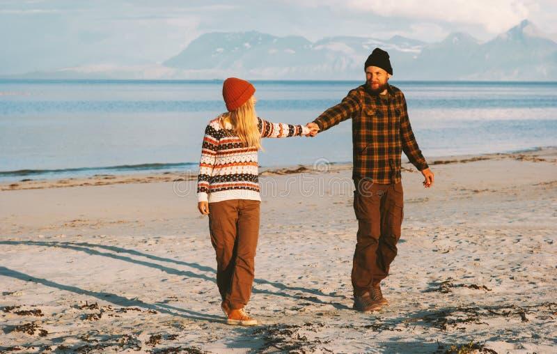 Koppla ihop att gå tillsammans på den strandmannen och kvinnan som rymmer händer royaltyfri bild